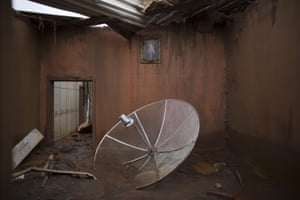 A satellite dish sits amid debris in a home destroyed when dams of an iron ore mine burst, causing a mudslide, in the village of Bento Rodrigues, Brazil