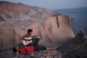 A young Iranian man plays guitar after sunset, on Hormoz