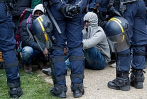 Calais camp evictees sit and crouch on the floor to rest as they wait, hemmed in by French riot police, for their turn to enter the processing centre.