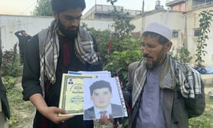Mohammed Jan Sultani's father, Ali, right, looks at his son's Taekwondo championship certificates along with picture of him.
