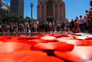 Members of the public place floating poppies onto a pond during a service at the Anzac memorial