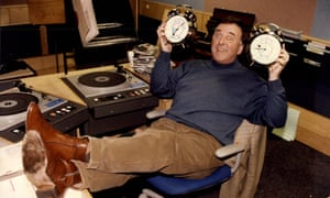 Terry Wogan in a radio recording studio, feet up on the table, holding two alarm clocks and grinning with raised eyebrows
