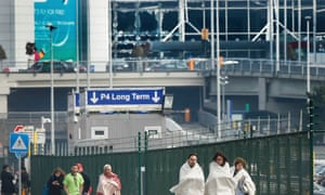People wrapped in blankets leave the scene of explosions at Zaventem airport.