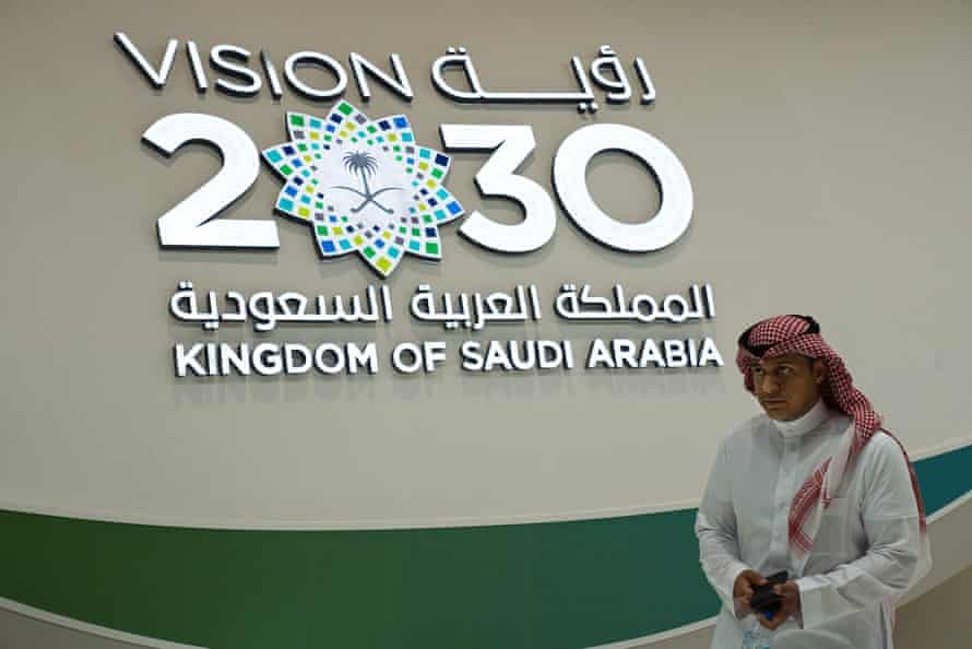 A Saudi man walks past a Vision 2030 display at a stand about Saudi Arabia during 2019's World Energy Congress in Abu Dhabi