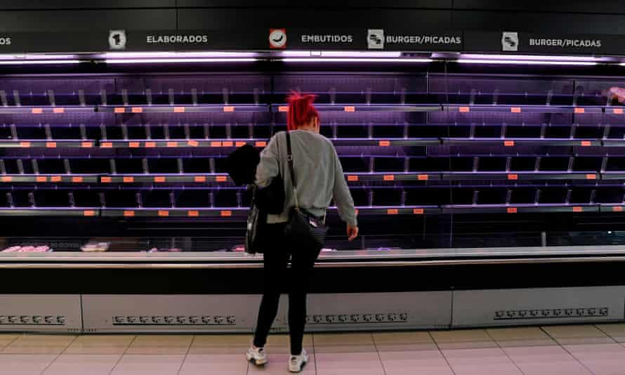 A woman does the shopping at a supermarket with empty shelves in Madrid.