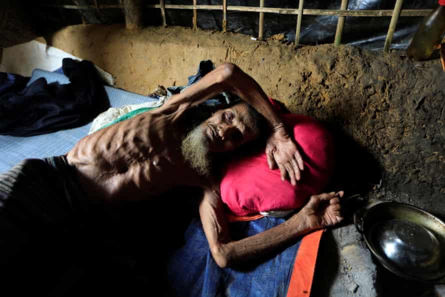 A Rohingya man lies at his shelter in Kutupalong refugee camp in Cox's Bazar, Bangladesh