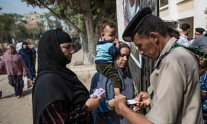 Egyptian security forces check documents of voters outside a polling station