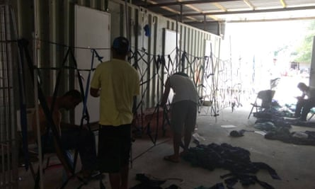 Refugees build a makeshift fence with fabric at the Manus Island detention centre.