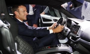 President Emmanuel Macron sits inside an Alpine car during a visit to the Paris motor show on 3 October.