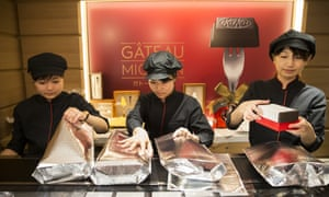 Employees pack boxes of KitKats into thermal bags. Behind is the advert for the Gateau Mignon KitKat.