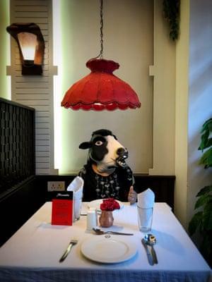 A woman dressed as a cow at a diner.