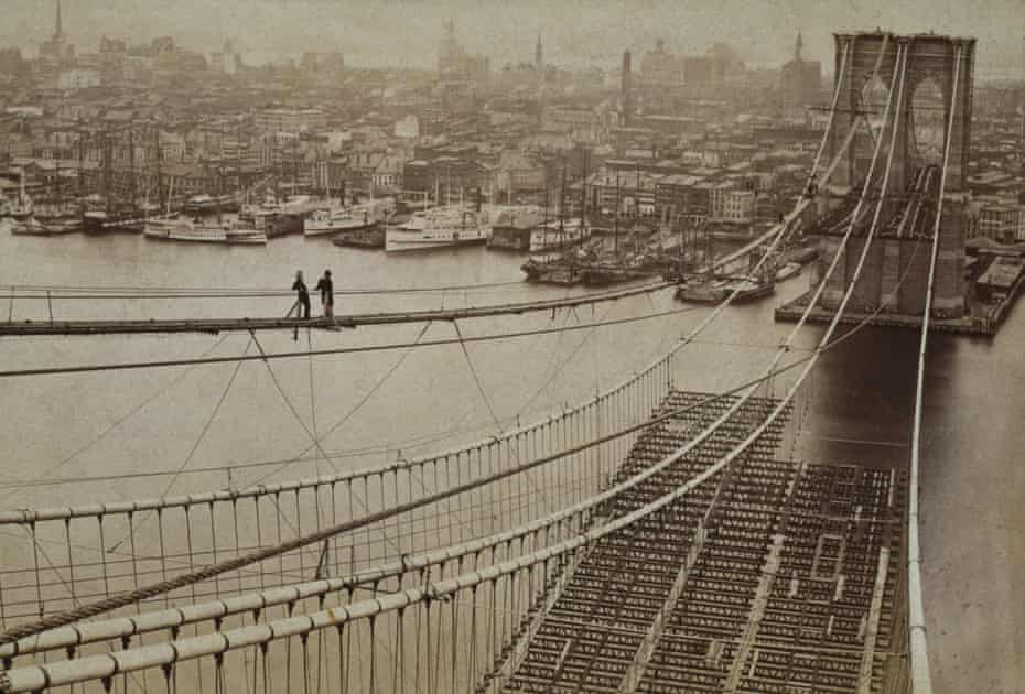 Two men survey the construction of the Brooklyn Bridge with Manhattan in the background, 1877.