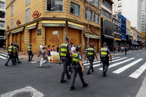 Members of Brazilian police patrol in front of closed stores due to the coronavirus pandemic at 25 de Marzo street, the major commerce centre in São Paulo, Brazil, 26 December 2020.