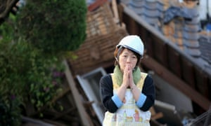 A woman in front of a collapsed house in Mashiki town