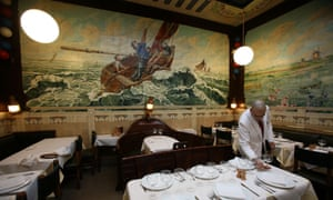 Image shows a waiter laying a table at Restaurant Vincent on Rue des Dominicains, Brussels, Belgium.