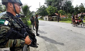 Members of Muslim rebel group Moro Islamic Liberation Front stand guard in the town of Sultan Kudarat ahead of the surrender of combatants with their firearms to President Benigno Aquino III.