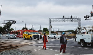 Pedestrians cross the railway lines that mark the border of the Iron Triangle neighbourhood of Richmond, which is known for its high crime rate.