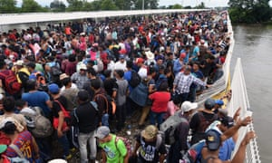 Honduran migrants taking part in a caravan to the US wait to cross to Mexico.