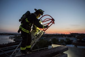 Recruit Giusti completes a ladder dismount as friends and family watch below. Before graduating, recruits organize a demonstration night to show their loved ones the skills they've learned during training