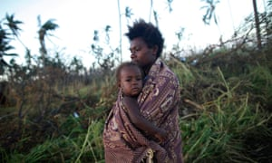 A woman carrying her baby walks past fallen trees in Tanna