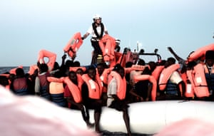 Migrants are taken aboard the Aquarius, a search and rescue ship