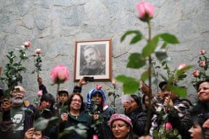 Bogota, ColombiaPeople hold flowers in front of a portrait Fidel Castro