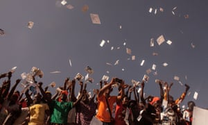 crowds throw pamphlets at a political rally in ouagadougou burkino faso