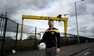 Dave McGreevy in a team shirt standing in front of two very large yellow cranes bearing the logo 'H&W'
