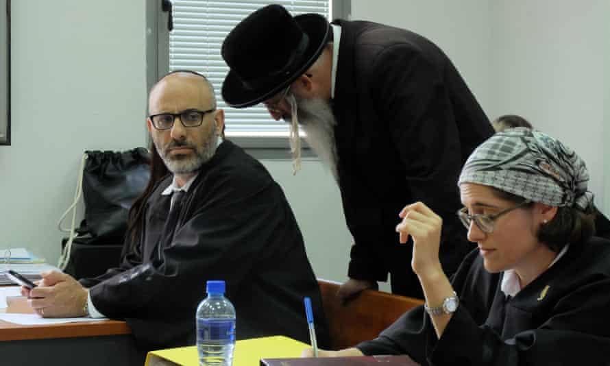 Malka Leifer's brother, centre, speaks with her defence lawyer Yehuda Fried at an extradition hearing in Jerusalem in 2016