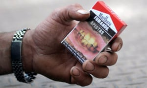The warnings on this cigarette packet read 'Smoking, you stink,' top, and 'Smoking causes bad breath', photographed in Montevideo in 2010.