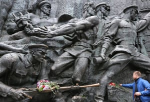 A man places flowers on the bronze monument at the World War II museum complex in Kiev, Ukraine