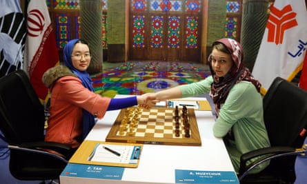 Chinese player Tan Zhongyi (left) shakes hands with Anna Muzychuk (right) of Ukraine at a championship in Iran