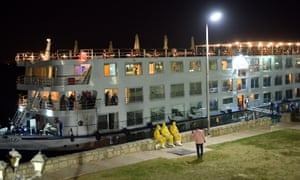 Egyptian health officials wearing protective suits sit in front of the River Anuket cruise ship where 45 people on board were diagnosed with coronavirus, in Luxor, Egypt, 07 March 2020.