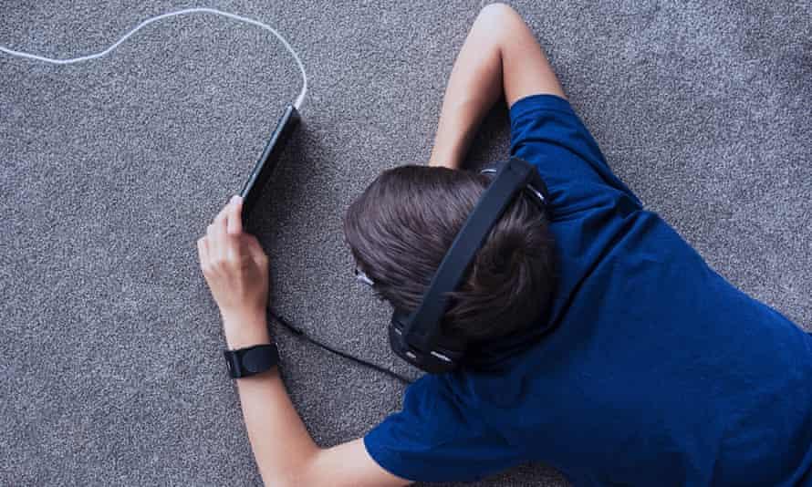 Boy using cell phone on floor