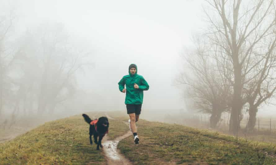 Active young man jogging with his dog.