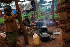 Godrieve Ndengakurio, 30, prepares lunch in a rudimentary kitchen next to her tent in the Nduta camp