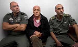 Israeli nuclear whistleblower Mordechai Vanunu, centre, sits between two prison guards as he waits in a courtroom before a hearing in Jerusalem.in 2010 for violating the conditions of his 2004 release.