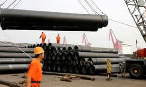 Workers in China loading huge steel pipes