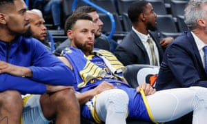 Stephen Curry watches from the bench with his team losing in the fourth quarter