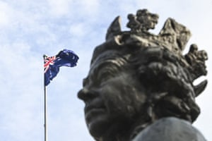The Australian flag flies next to a statue of her Majesty the Queen Elizabeth II at Parliament House in Canberra.