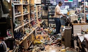 An employee stands behind the counter of a gas station and liquor store amid fallen bottles after the earthquake in Ridgecrest, California, on 6 July.