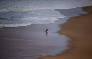 A surfer enters the water during a surf session at  Praia do Norte in Nazaré, Portugal,