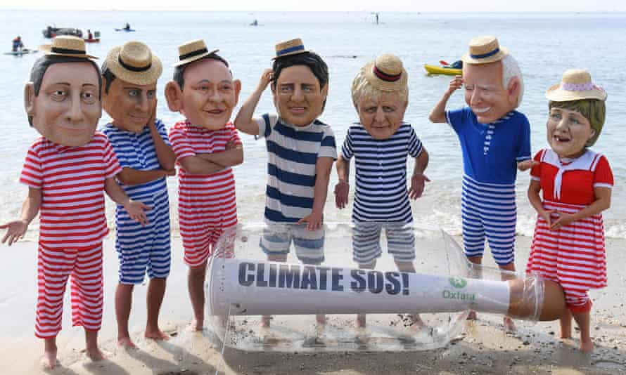 Oxfam campaigners pose as G7 leaders on Swanpool Beach near Falmouth, Cornwall.