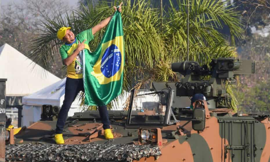 A supporter of President Jair Bolsonaro holds a Brazilian national flag while standing on a military vehicle, outside the Alvorada Palace, during the Independence Day celebrations in Brasília on Tuesday.