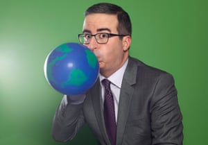 Comedian John Oliver blowing up a balloon with the world on it