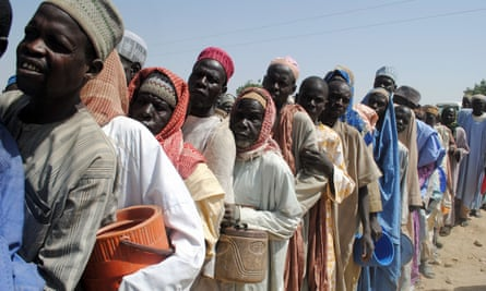 People wait to be served food at Dikwa Camp, in Borno state, north-eastern Nigeria