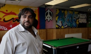 Hanif Qadir standing in a room with a pool table and graffiti-style art on the wall