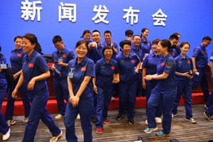 Staff members of the Jiuquan satellite launch centre share a light moment before a briefing the day before the launch