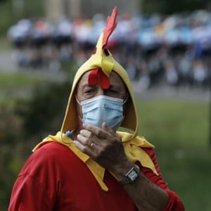 A spectator dressed up as a rooster wearing a mask stands along the road of the ninth stage from Pau to Larun.