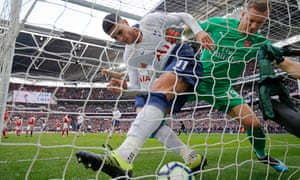 Erik Lamela of Tottenham Hotspur and Bernd Leno of Arsenal battle for the ball after Harry Kane had scored the Spurs equaliser from the penalty spot during the Premier League match at Wembley Stadium